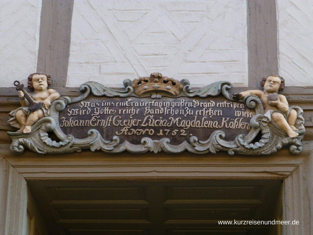 Das Bild zeigt eine Türüberschrift eines Hauses in Wernigerode im Harz.