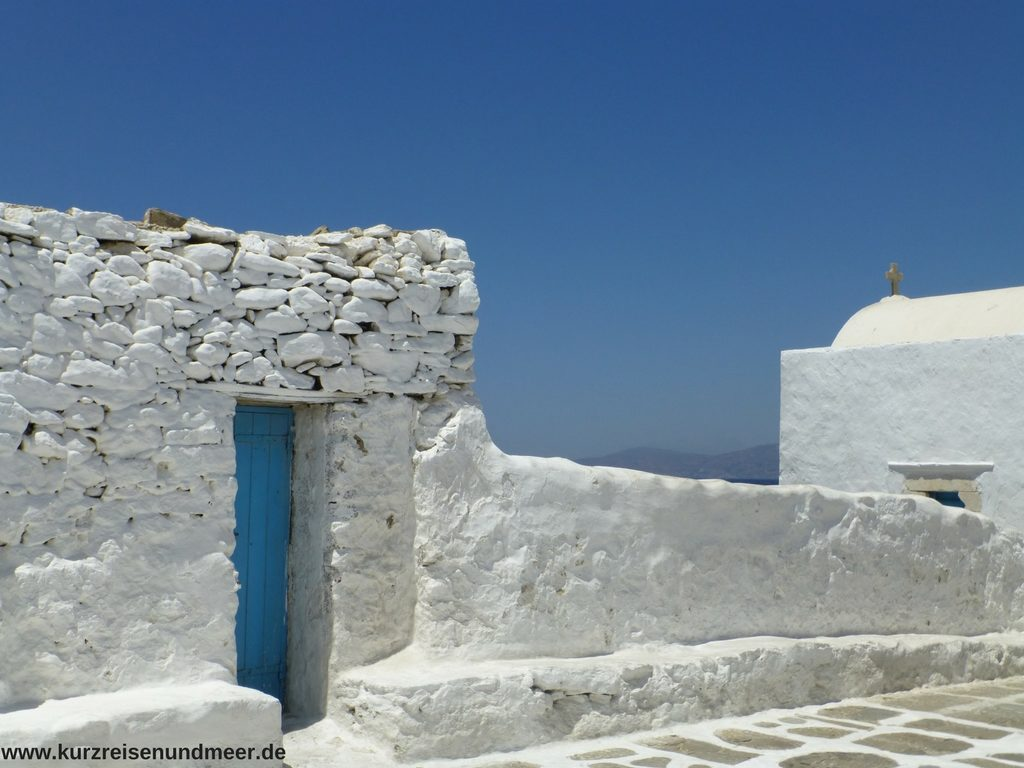 Blaue Tür in einer weißen mauer auf Mykonos