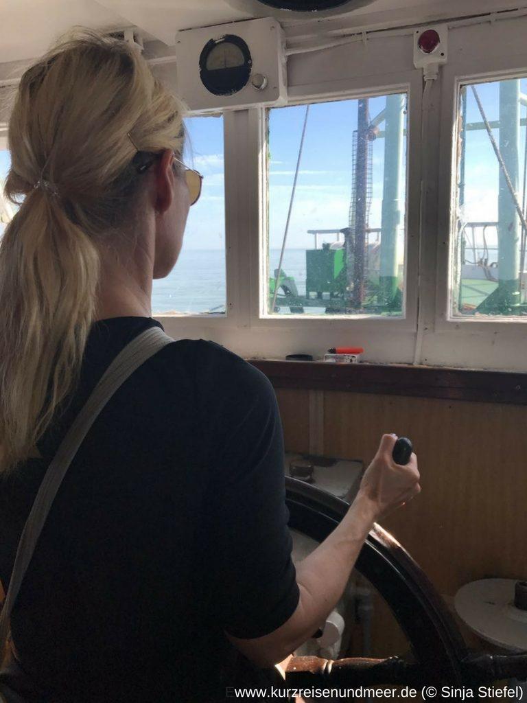 Das Bild zeigt Kerstin am Steuerrad. Man sieht den Kutter und das Meer.