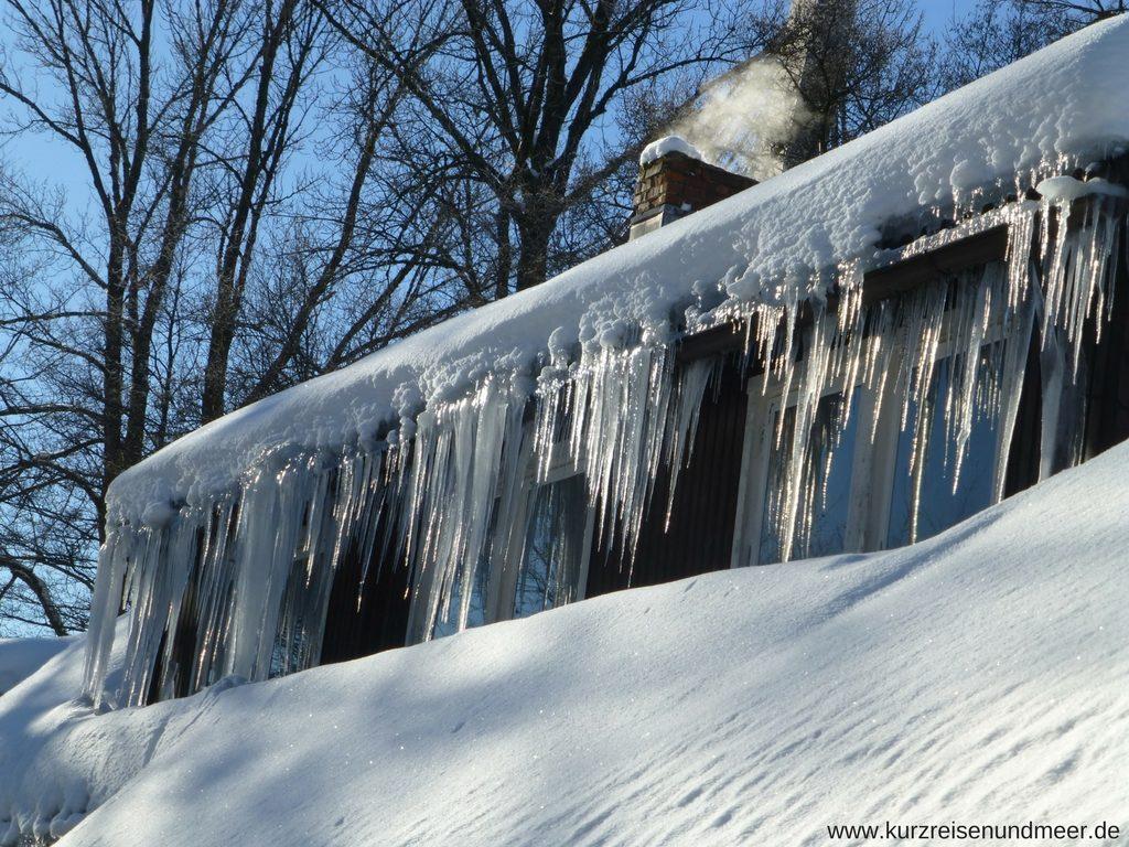 Das Bild zeigt ein Haus, an dessen Dachrinne lange Eiszapfen hängen