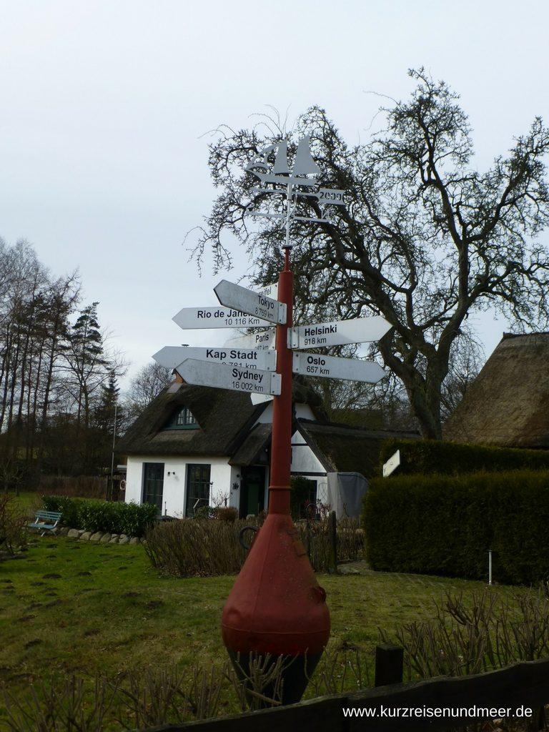 Boje in einem Dorf auf Rügen zeigt Entfernungen in verschiedene Hauptstädte an (Beitrag zur Foto-Blogparade)